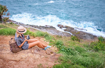 Photoshooting and traveling. Young woman in hat with rucksack holding camera enjoying sea view.