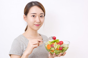 Healthy lifestyle concept. Young woman eating salad.