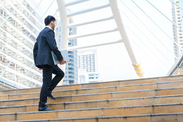 Business man celebrating success. Young businessman walking at stairs and hold laptop computer while standing outdoors with office building in the background.