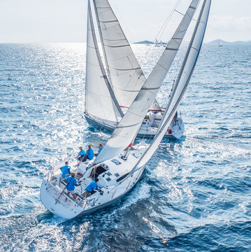 Sailing boats from bird view crossing open sea