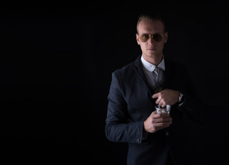 Portrait of handsome man in a suit hiding gun front his back and holds whiskey with looking at the camera on black background.