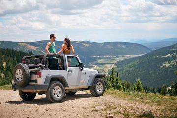 Road trip couple in four wheel convertible in Rocky mountains, Breckenridge, Colorado, USA