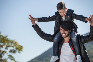 Father and son outdoors, father carrying son on shoulders