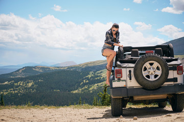 Young woman on road trip climbing into parked off road vehicle, Breckenridge, Colorado, USA