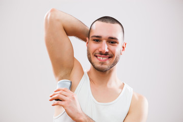 Young man is applying antiperspirant to his armpit.
