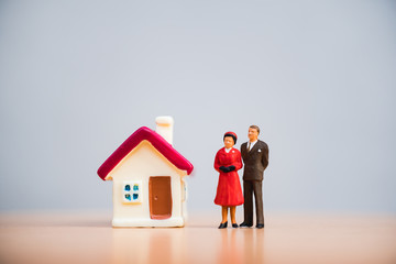 Miniature people, closeup man and woman standing with mini house using as relationship and family concept