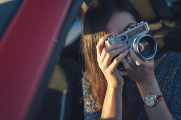 Woman taking photos from car with vintage camera