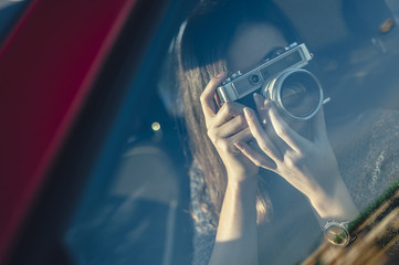 Portrait of woman taking photos from car with vintage camera with glass reflection