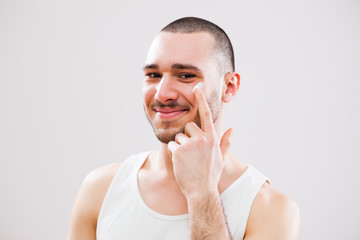 Young man who is applying skin cream on his face.