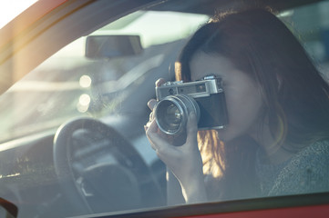 Portrait of woman taking photos from car with vintage camera and lens flare