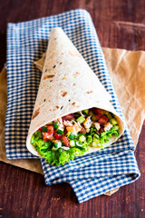 Freshly baked tortilla wrap with cucumbers, tomatoes, lettuce, prawns, avocado and bell pepper for breakfast or summer picnic snack