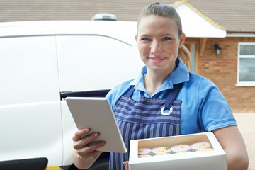 Portrait Of Female Baker With Digital Tablet Making Home Delivery Of Cupcakes
