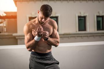 Portrait of muscular shirtless man posing outdoors.