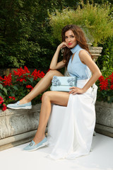 Elegant, posh and stylish young lady with makeup and hairstyle is posing near the beautiful mansion, in the park, flowers and leaves at the background. Summer photoshoot of attractive woman