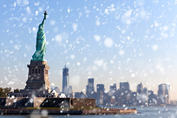 The Statue of Liberty free of tourists and New York City Downtown on sunny early morning during snowfall.