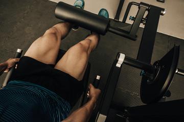 Closeup nice muscle runner legs with leg machine, Sport concept.