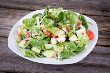 Chicken and vegetable salad with ranch dressing over wooden background table
