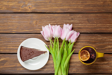 Cup of english tea with spring tulips and cake