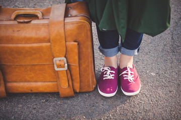 Girl foots in gumshoes with travel bag