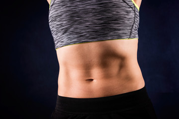 Woman`s flat stomach with press. ABS. Isolated on dark blue background. Workout concept.