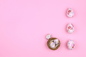 Happy Easter Day. Tradition easter big and small eggs with spring's flower's pattern in wooden nest on pink background