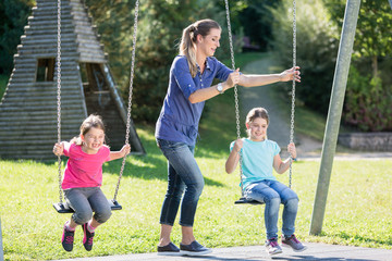 Happy family with two girls and mother on playground swing