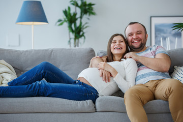 Image of happy pregnant woman and man on gray sofa