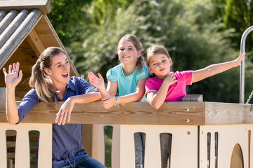 Happy family with kids playing in tree house on playground