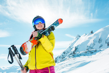 Photo of smiling woman with snowboard on background of snowy hills
