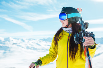 Photo of sports girl looking sideways in helmet, mask with skis