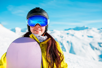 Photo of smiling woman in helmet and mask with snowboard on background of snowy hills
