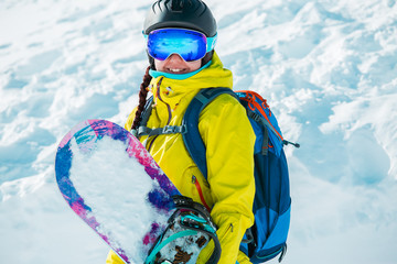 Photo of smiling woman in helmet and with snowboard in background of snowy landscape