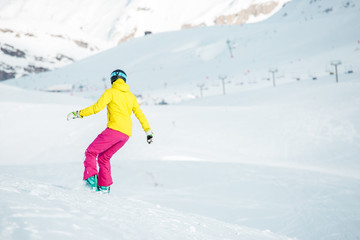 Image from back of girl in sports clothes snowboarding