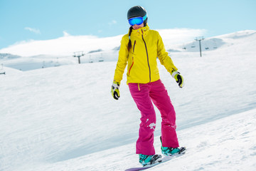 Picture of young athlete girl wearing helmet in sports clothes snowboarding