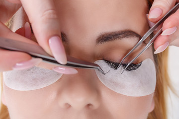 Eyelash Extension Procedure. Woman Eye with Long Eyelashes. Lashes, close up, selected focus.