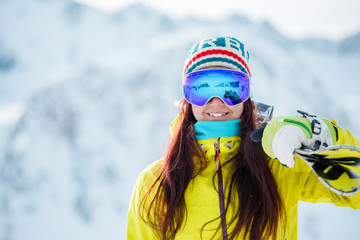Image of woman in mask with skis on her shoulder against snowy hill background