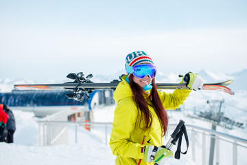 Photo of smiling sports woman with skis on her shoulder