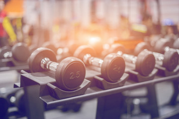 Rows of dumbbells in gym interior with equipment