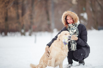 Image of smiling woman squatting next to labrador with toy in teeth in winter park