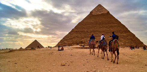Three tourists are riding camel and moving to the pyramid