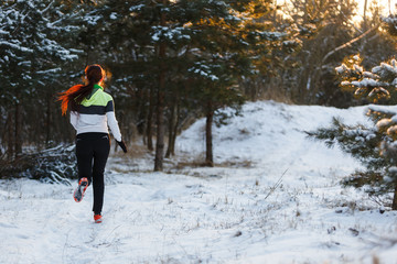 Image from back of athlete in sneakers on morning run against background of trees in winter