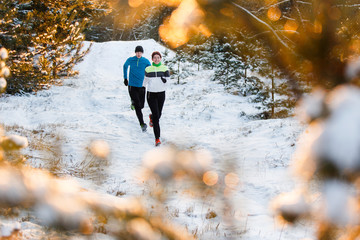 Photo of running sports woman and man in winter park