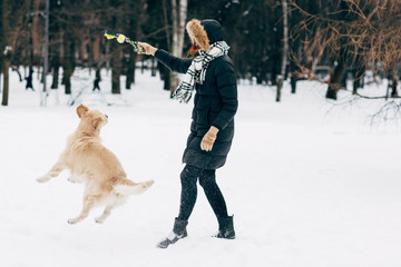 Picture of woman playing with retriever in winter