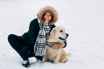 Image of smiling woman with dog in winter park