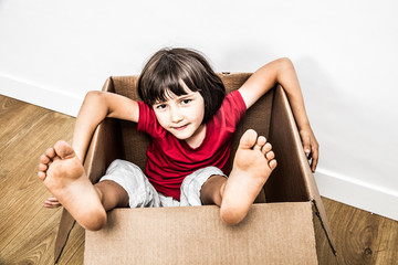 relaxed child sitting in old cardboard box with feet out