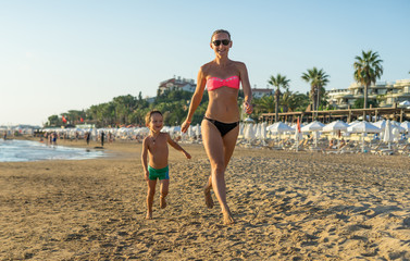 Happy little boy with young beautiful mother running on summer beach. Positive human emotions, feelings, joy. Funny cute child making vacations and enjoying summer. On the Sunset.