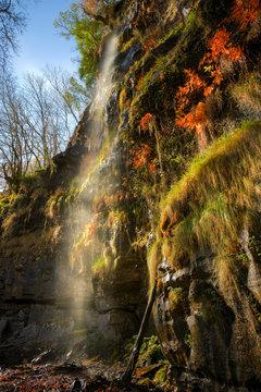 Small stream rushes down a limestone cliff