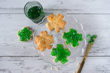 Saint Patrick's Day shamrock biscuits with green jelly and gold knife top view
