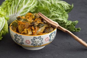 Stewed cabbage in bowl on grey background.