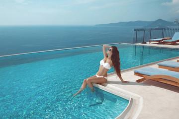 Sexy model in white bikini sunbathing by infinity swimming pool. Luxury travel vacation. Brunette Woman sunbathing at luxurious resort. Beautiful destinations concept.